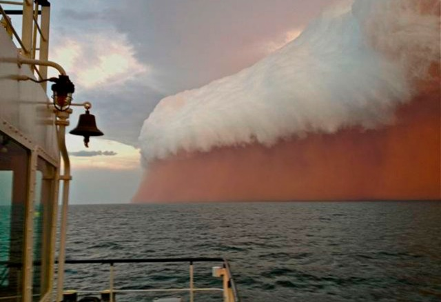 A dust cloud capped by clouds sweeping across the Indian Ocean west of Australia. (The dust was once part of Australia.) [Reuters/Brett Martin/fishwrecked.com]