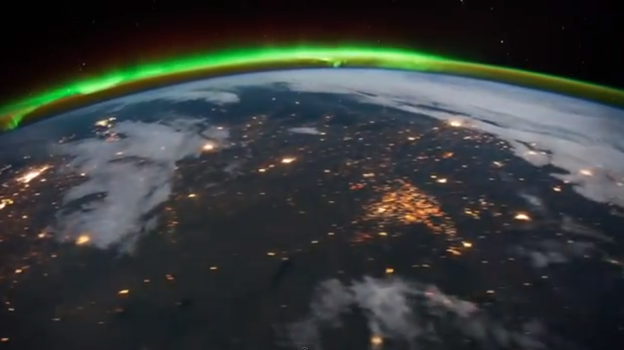 A green aurora in the distance, the gas flares on the Bakken oil patch in the foreground. The flares are from fracking wells. North Dakota is now the second largest oil producing state. (Texas is first.) [cap from International Space Sation video via Krulwich's blog at npr.org]