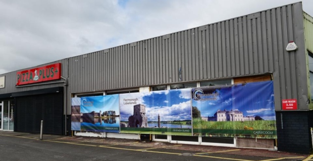 Some problems are too large for a complete counterfeit. This abandoned shopping center has big scenic posters pasted over the dead-eyed windows. [Photo: Bryan O'Brien for the Irish Times]