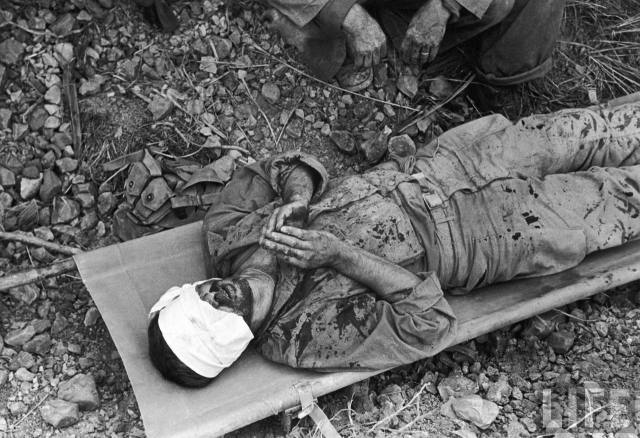 "Okinawa, 1944. Smith: ""In his first action he had been quickly hit and was now lying on a stretcher... The blood had sprayed the length of him and behind him as he ran... it now was mixed with the muck of Okinawa from his boots to the head wound from which it had come... As he lay thee he touched the tips of his fingers together... The last I saw of him...two men running and creeping with the recent replacement between them... I think the boy on the stretcher was already dead."""