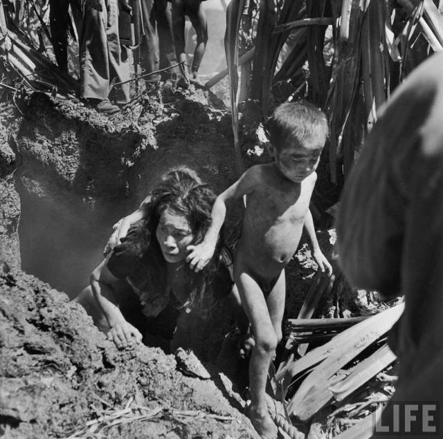 "Saipan, 1944. Smith: ""They burst out through the opening, stumbling, dazed, choking, and nearly blinded by the fumes, trying to lurch and claw their way past the still warm body of a man, and another of a boy. Trying for an escape when there was no escape."""