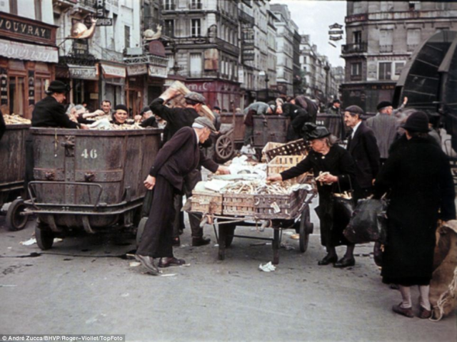 People rummaging through scraps at a market in occupied Paris. [photo by André Zucca, who took pictures for the Germans.]