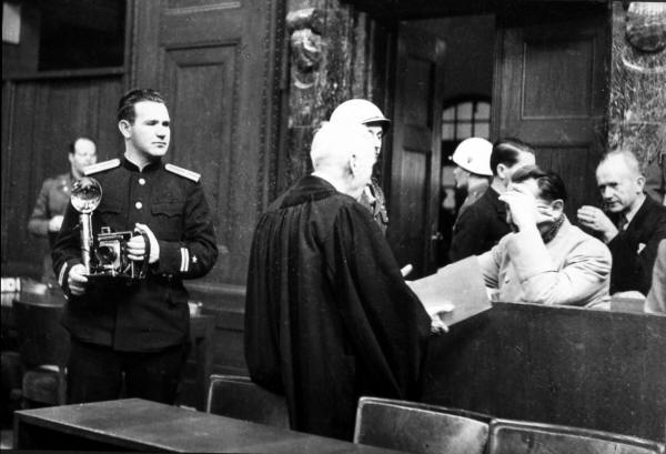 Khaldei at Nuremburg. Goring is in the dock, possibly shielding his eyes from the glare. The defendants began wearing dark glasses soon after.